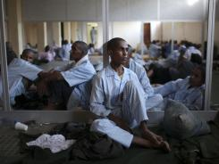 Pro-Gadhafi soldiers rest in a school converted into a prison in Tripoli.  As opposition fighters celebrate, a defiant Moammar Gadhafi has yet to be found.