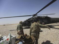 A U.S Army flight medic and medical nurse carry a wounded Afghan soldier to a medevac helicopter.