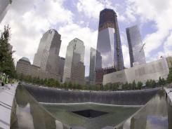 From the ruins of the World Trade Center, a  new skyline of Lower Manhattan rises over a waterfall.