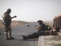 Libyan rebels guard an area between Tarhouna and Bani Walid on Tuesday. A core group of aides to toppled dictator Moammar Gadhafi, reportedly have deserted.