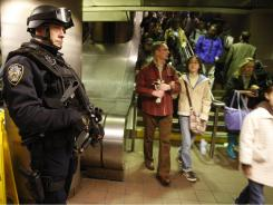 "Todd Sessa keeps his eye on commuters entering and exiting the subway system at Grand Central Station in New York as part of ""Operation TORCH,"" or Transit Operational Response with Canine and Heavy Weapons, funded by a grant from the Department of Homeland Security."