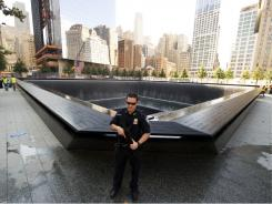 A port authority officer stands guard near the reflecting pool of the World Trade Center Memorial before the 10th anniversary of 9/11.