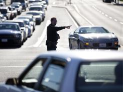 A San Diego police official directs traffic after a power outage Thursday in San Diego.