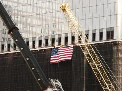 Construction workers hang a flag from the side of 1 World Trade Center in New York.