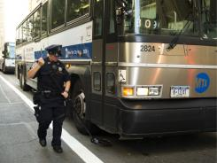 A New York City police officer inspects a bus Friday near the World Trade Center in New York. Police in New York remain on alert after reports of a terror threat.