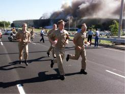 Military personel flee from the Pentagon after a plane crashed into the building Sept. 11, 2001.