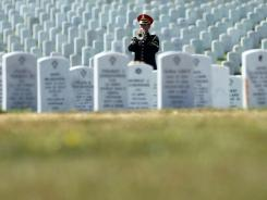 The bugler plays 'Taps' during the funeral of the late Army Spc. Jordan C. Schumann of Port Saint Lucie, Florida, August 9, 2011 at Arlington National Cemetery in Arlington, Virginia.