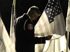 Firefighter Lt. Joe Huber of Bronx, N.Y., who helped catalog remains at Ground Zero, reads names on flags in Lower Manhattan early Sunday before speaking at a sunrise ceremony.
