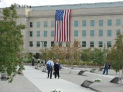 A flag marks where terrorists flew a plane into the Pentagon as families and guests walk through the memorial to the victims on Sunday, the 10th anniversary of the attacks.