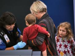 A young traveler undergoes a pat-down by a Transportation Security Administration agent at Denver International Airport last November.