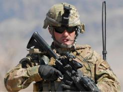 In Afghanistan: Army 1st Sgt. Raymond Dakos patrols a village near Kandahar in March.