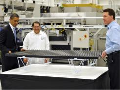 President Obama lifts a solar panel with CEO Chris Gronet during a tour of Solyndra, Inc., a solar panel manufacturing facility, last May.