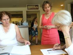 Annie Laurie Gaylor (standing),  co-president of the Freedom from Religion Foundation, talks with Phyllis Rose, right, as Sue Barry works at the group's headquarters in Madison, Wis.