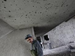 An Afghan policeman passes by a shattered wall as he visits the building that was occupied by Taliban militants in Kabul, Afghanistan, on Wednesday.