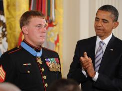 President Obama applauds Marine Sgt. Dakota Meyer after awarding him the Medal of Honor.