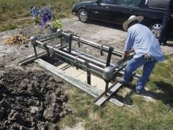 Juan Acosta, with Corpus Christi Wilbert Vaults, slowly lowers the casket of Robert Nelson, 62, into the ground on Aug. 8. Nelson was buried under the Nueces County indigent burial program because no family members could be located.