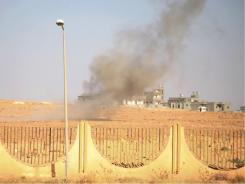 Smoke rises as a rocket explodes at the northern gate of Bani Walid, Libya.