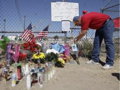 Sean Moran picks up a petal Sunday from a memorial near the site of a crash at the National Championship Air Races in Reno.