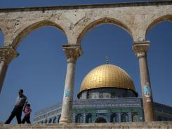 A Palestinian man and child walk past the Dome of the Rock mosque on Sunday in the Al-Aqsa  compound in Jerusalem.