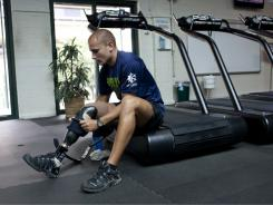 Joseph Kapacziewski adjusts his prosthetic leg before a workout at Walter Reed Army Medical Center in May.