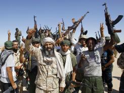 Libyan fighters chant slogans as they take control of Gadhafi loyalist villages Saturday in Lansfol, Libya.