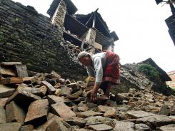 A Nepalese woman removes bricks from a damaged house to make way for pedestrians Monday after an earthquake in Katmandu, Nepal.