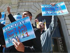 Former Navy petty officer Joseph Rocha, left, holds a sign Tuesday during a news conference in San Francisco.