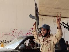 Revolutionary fighters celebrate as they gather at a strategic checkpoint before heading on a  mission in Sirte, Libya.