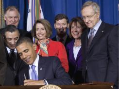 "Lawmakers and supporters look on as President Barack Obama signs ""don't ask, don't tell"" repeal legislation, Wednesday, Dec. 22, 2010, at the Interior in Washington."