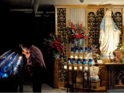 Judy Martin of Berlin, Wis., lights a votive candle in the crypt at the Shrine of Our Lady of Good Help.