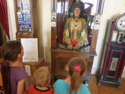 Children examine an antique Gypsy fortuneteller machine that sat for decades in a Virginia City, Mont., restaurant. Collectors say the 100-year-old machine that speaks players' fortunes may be the last of its kind.