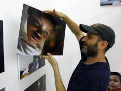 Photographer Danny Goldfield arranges a picture in his exhibition of photographs celebrating New York children from more than 160 different countries on Wednesday at the Park 51 mosque gallery space.