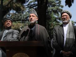 Afghan President Hamid Karzai is flanked by vice presidents Mohammad Qasim Fahim and Mohammed Karim Khalili as he addresses media representatives during a Thursday news conference.