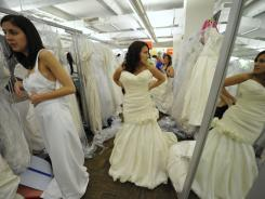 """Women try on wedding dresses at the """"Running of the Brides"""" sales event at Filene's Basement in New York on June 3. The median age of first marriage has increased during the recession for men and women."""