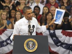President Obama holds up the American Jobs Act as he speaks at North Carolina State University in Raleigh, N.C., on Sept. 14.