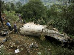 Nepalese rescue workers and civilians gather at the wreckage of a plane after it crashed in the mountains outside Bisankunarayan village, just south of Katmandu, Nepal, early Sunday.