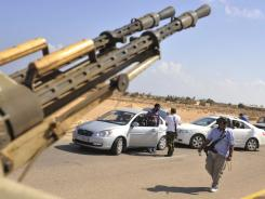 Internally displaced Libyans wait at the check point of revolutionary fighters near Sirte, Libya, on Wednesday.
