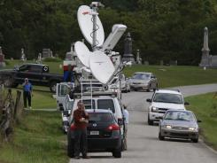 Media set up Monday near the property where serveral bodies were found on Stipps Hill Road in Franklin County, Ind.