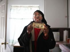 Dwanna Myree, of Detroit, holds up $10, which is all she has for the next five days.