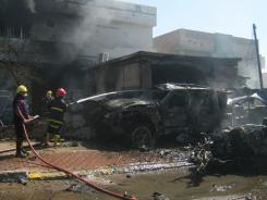 Iraqi firefighters extinguish flames after a car bomb attack in Kirkuk.