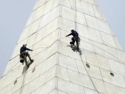 Daniel Gach, left, and Emma Cardini dangle by a rope more than 500 feet above ground as they inspect the exterior of the Washington Monument on the National Mall on Thursday.
