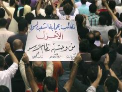 "Anti-regime protesters  hold up an Arabic placard reading: ""We demand to protect the unarmed Syrian people from the brutality of Assad's regime."""