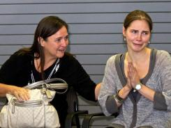 Amanda Knox, right, acknowledges supporters Tuesday while her mother, Edda Mellas, comforts her during a news conference at the Seattle airport.