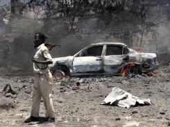 A Somali soldier keeps guard near burned bodies and a burning vehicle at the scene of an explosion in Mogadishu.