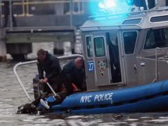 A victim's body is pulled from the East River after a commercial helicopter crash on Tuesday in New York City.