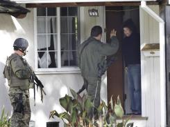 Police interview a resident in a Cupertino, Calif., neighborhood on Wednesday as a shooting suspect remains at large.