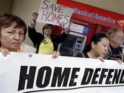 Myrian Munoz, of Pacifica, Calif., left, and Lili Lu, of Fremont, Calif., right, members of the Home Defenders League, rally in front of the Bank of America in San Jose, Calif., June 3.