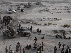 Yemeni army forces rest at the southern city of Zinjibar, Yemen, after freeing it from al-Qaeda-linked militants Saturday.