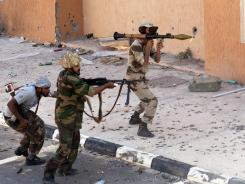 National Transitional Council (NTC) fighters take part in a street battle recently in Sirte.