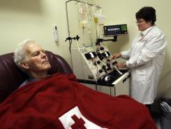 A nurse hooks a blood infusion machine to treat a patient for prostate cancer.